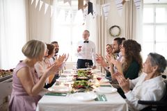 Uma família grande que senta-se em uma tabela em uma festa de anos interna, um homem superior que dá um discurso fotos de stock