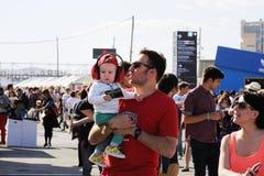Uma família, incluindo uma criança do bebê com protetores do som da orelha, caminhada no festival 2013 do som de Heineken Primaver Foto de Stock Royalty Free