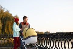 Uma família loving nova anda pelo lago com um carrinho de criança Sorrir parents pares com o pram do bebê no parque do outono Amo imagem de stock