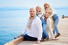 Uma família nova, amigável: o pai, a mãe e duas filhas sentam o foto de stock
