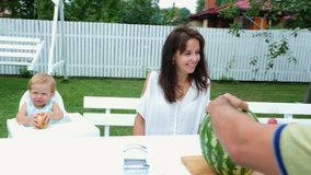 Uma família nova com as duas crianças engraçadas pequenas que sentam-se em uma tabela de jantar no jardim, no verão O paizinho co video estoque