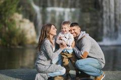 Uma família nova feliz em um fundo da cachoeira fotos de stock royalty free