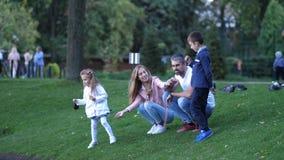 Uma família nova feliz O pai, o filho, a mãe e a filha alimentam os pássaros no parque com pão 4K Movimento lento filme