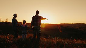 Uma família nova - a mamã, o paizinho e a filha olham junto o por do sol Feliz junto, silhuetas no por do sol Vista traseira video estoque