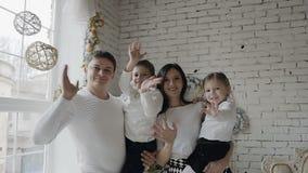 Uma família nova no fundo de uma parede branca que olha na câmera e que acena seus cumprimentos das mãos video estoque