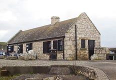 Uma família pequena aprecia o café no centro da loja e do visitante no porto bonito de Ballintoy na costa norte do condado Antrim imagem de stock royalty free