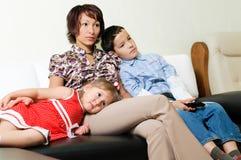 Uma família que presta atenção à tevê Fotografia de Stock