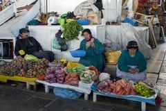 Uma família senta-se em sua tenda das frutas e legumes em um mercado em Cusco no Peru Fotos de Stock