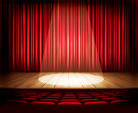 Uma fase do teatro com uma cortina vermelha, assentos e um projetor