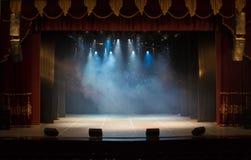 Uma fase vazia do teatro, iluminada por projetores e por fumo fotos de stock