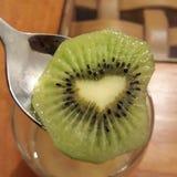 Uma fatia coração-dada forma de fruto de quivi fresco imagens de stock