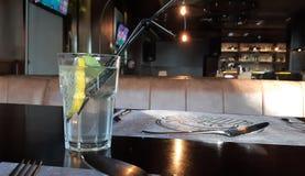 Uma fatia de laranja em um vidro com água gasosa Um vidro da água com uma fatia de limão, fotografia de stock