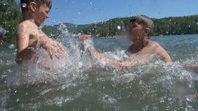 Uma fatura ativa de três meninos espirra na água filme