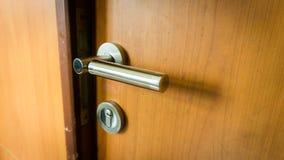 Uma fechadura da porta com os fechamentos de madeira da porta e do metal e o botão de porta foto de stock