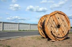 Uma ferida do cabo bonde do poder em uma bobina de madeira contra o céu azul Foto de Stock Royalty Free