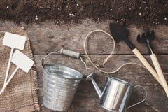 Uma ferramenta de jardim, uma pá, um ancinho, uma lata molhando, uma cubeta, tabela Imagem de Stock