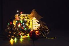 Uma festão de incandescência em um frasco de vidro e decorações do Natal em um fundo de madeira escuro Ano novo, cartão do Natal  Foto de Stock Royalty Free