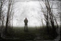 Uma figura encapuçado assustador posição na borda da floresta Em uma noite nevoenta dos invernos Com um grunge, retro edite fotografia de stock