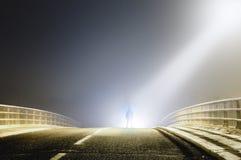 Uma figura encapuçado sinistra silhoutted por luzes brilhantes em uma estrada enevoada assustador na noite Com um Cyberpunk edite imagem de stock royalty free