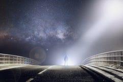 Uma figura encapu?ado sinistra silhoutted por luzes brilhantes em uma estrada enevoada assustador na noite Com um Cyberpunk edite fotografia de stock royalty free