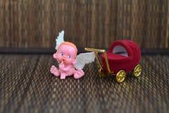 Uma figura pequena de um anjo que senta-se ou perto de um fim do carrinho de criança da guarda-joias em acima fotografia de stock