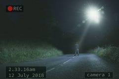 Uma figura solitária posição na estrada na noite ao olhar um UFO e um feixe de luz no céu Com um CCTV edite imagens de stock