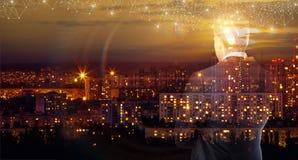 Uma figura transparente de um homem de negócios que olha a cidade da noite imagens de stock