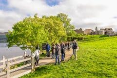 Uma fila dos turistas que esperam uma parte traseira do passeio do castelo de Urquhart fotos de stock royalty free