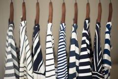 Uma fileira da marinha listrou partes superiores para mulheres em ganchos de madeira em um armário Imagens de Stock Royalty Free