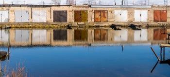 Uma fileira das portas da garagem que refletem na água fotos de stock