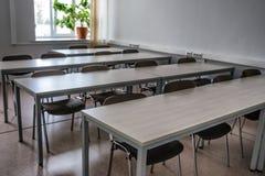 Uma fileira das tabelas e das cadeiras em uma sala de aula imagens de stock royalty free