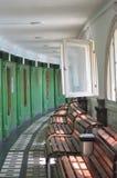 Uma fileira de bancos de madeira oposto a algumas portas verdes Imagens de Stock Royalty Free