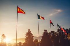 Uma fileira de bandeiras do voo das nações no fundo do céu do por do sol Bandeiras de países diferentes Imagem de Stock Royalty Free