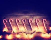 uma fileira de bastões de doces e de luzes de Natal tonificou com um efeito retro do filtro do instagram do vintage fotografia de stock