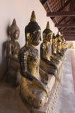 Uma fileira de Budas assentadas em um templo Fotografia de Stock Royalty Free