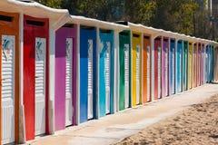 Uma fileira de cabanas da praia com as portas brilhantemente coloridas no Sandy Beach Fotos de Stock