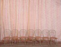 Uma fileira de cadeiras vazias contra uma cortina do teatro No thater Fotografia de Stock