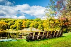 Uma fileira de cadeiras vazias sob o céu torrado dramático do outono sobre o lago Tyrrel no jardim de Innisfree, Millbrook, New Y Foto de Stock