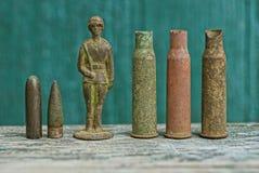 Uma fileira de cartuchos e balas velhas e um soldado de lata em uma tabela cinzenta fotografia de stock royalty free