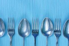 Uma fileira de colheres e de forquilhas cinzentas em uma tabela azul Fotografia de Stock Royalty Free