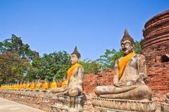 Uma fileira de estátuas antigas de buddha na frente do pagode da ruína Fotografia de Stock Royalty Free
