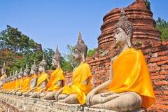 Uma fileira de estátuas antigas de buddha na frente do pagode da ruína Fotos de Stock Royalty Free