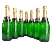 Uma fileira de sete garrafas de vidro verdes Foto de Stock