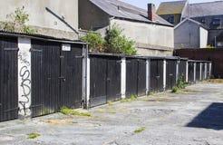 Uma fileira de típico trava acima garagens alugado com os telhados lisos no reparo pobre no condado para baixo Irlanda do Norte d Imagens de Stock Royalty Free