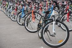 Uma fileira de um grande número bicicletas com as rodas no squa da cidade Foto de Stock Royalty Free