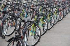 Uma fileira de um grande número bicicletas com as rodas no squa da cidade Fotografia de Stock