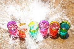 Uma fileira de vidros do arco-íris sob um chuveiro da água foto de stock