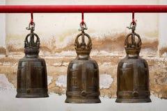 Uma fileira do sino grande do buddhism três no templo tailandês imagens de stock royalty free