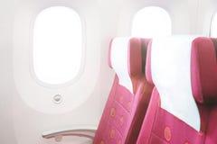 Uma fileira dos assentos e das janelas em uma cabine de aviões imagem de stock royalty free