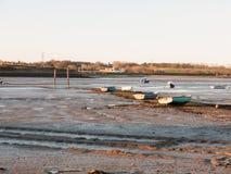 Uma fileira dos barcos estacionou na lama com a maré para fora Imagens de Stock Royalty Free